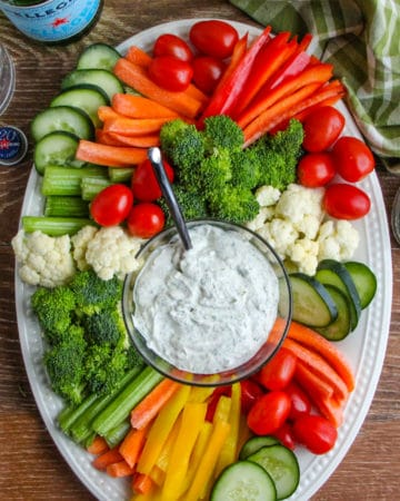 A tray of vegetables with ranch dip.