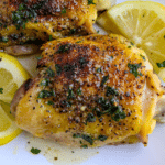 Lemon Pepper Chicken Thighs and lemon slices on a white plate garnished with chopped parsley