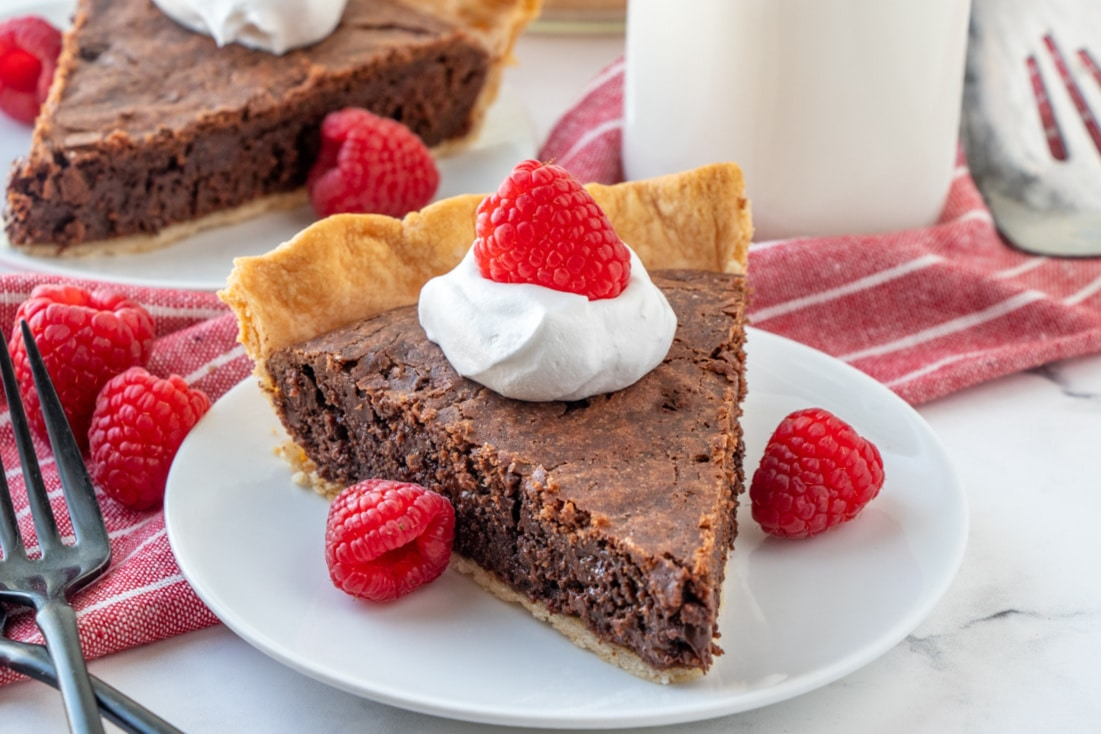a slice of brownie pie on white plate next to a glass of milk
