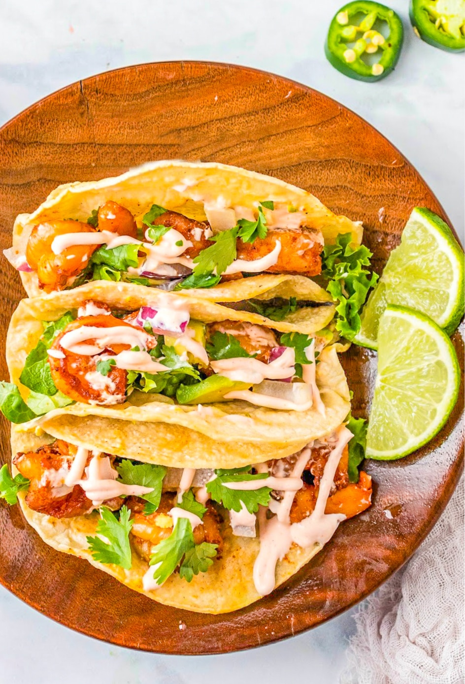 Prepared shrimp tacos on plate with lime slices.