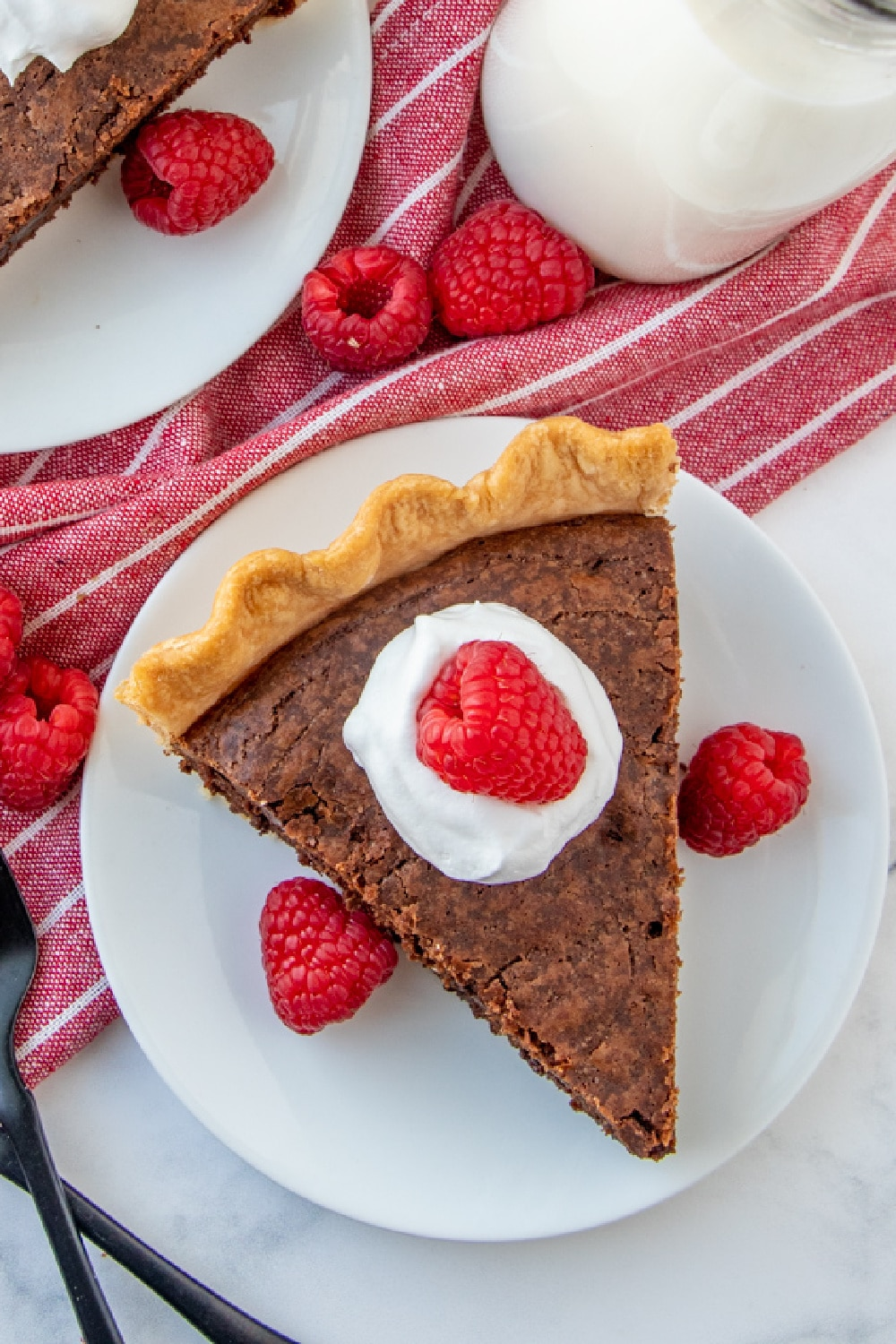 A slice of pie topped with whipped cream and raspberries.