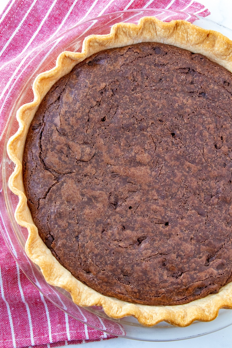 Brownie pie just from the oven in glass pie plate on a red dish towel