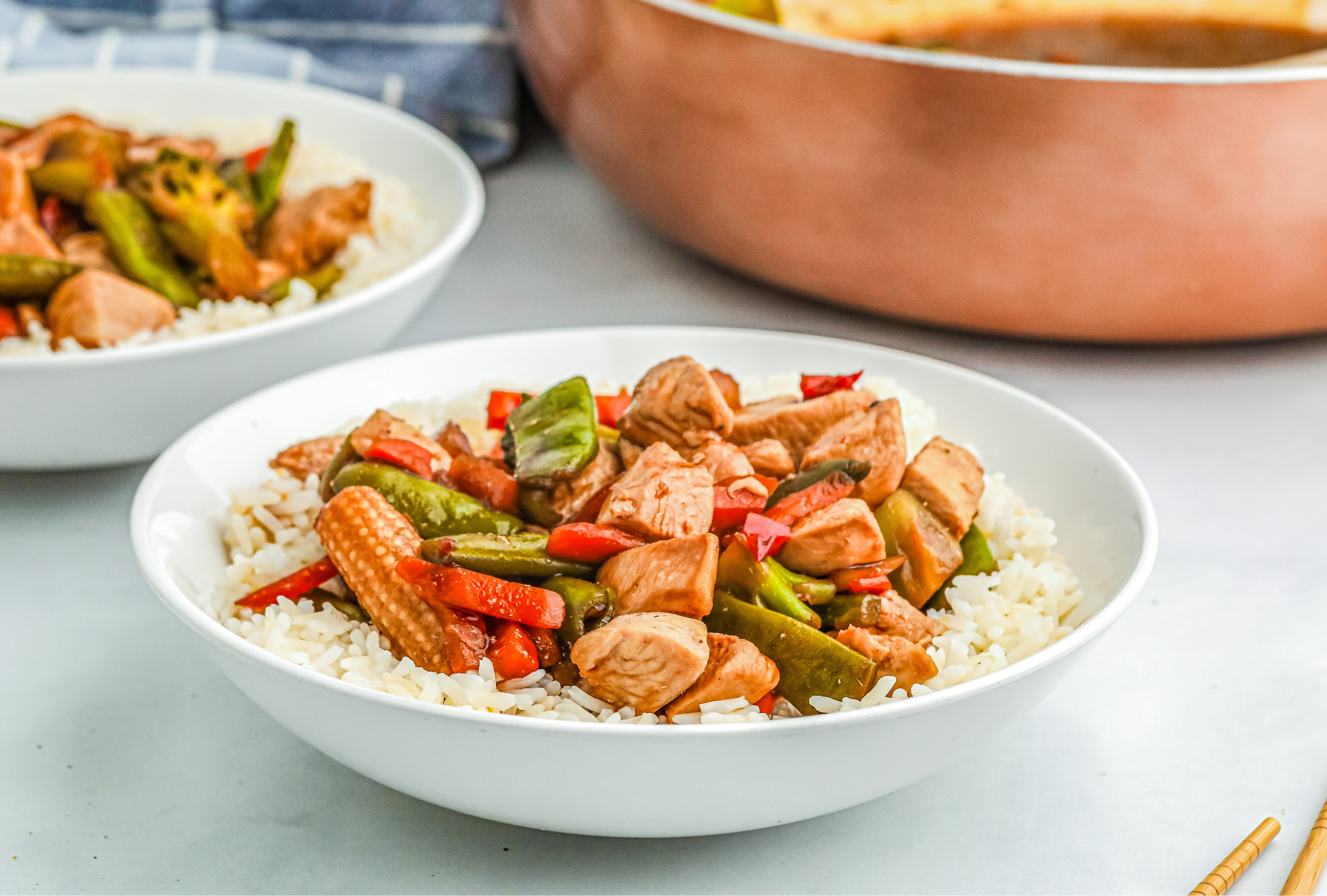 A white bowl of stir-fry over rice
