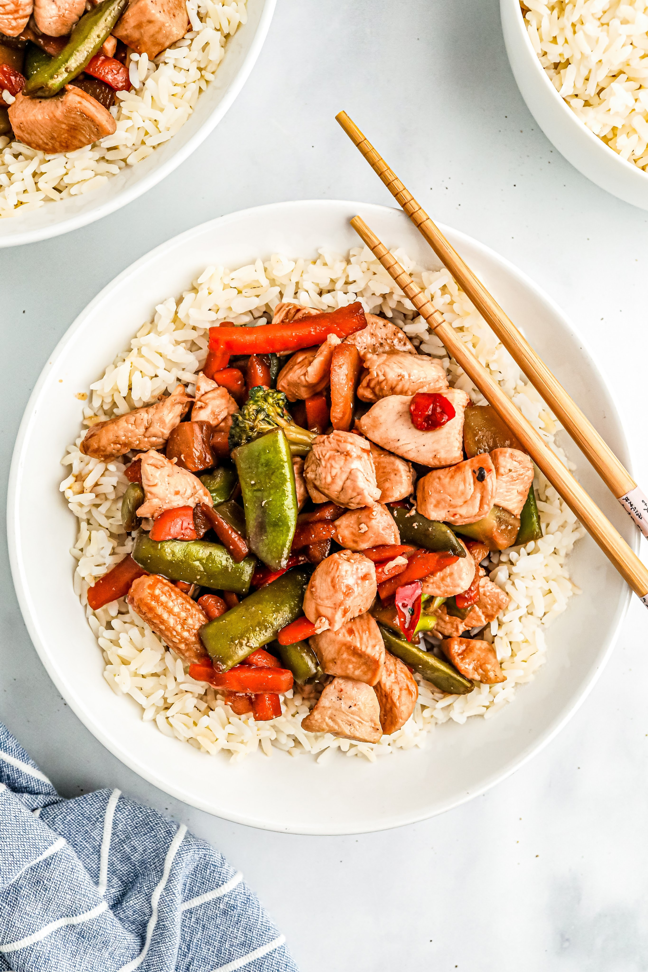 Chicken stir-fry over rice in a white bowl with chop sticks resting on edge of the bowl.