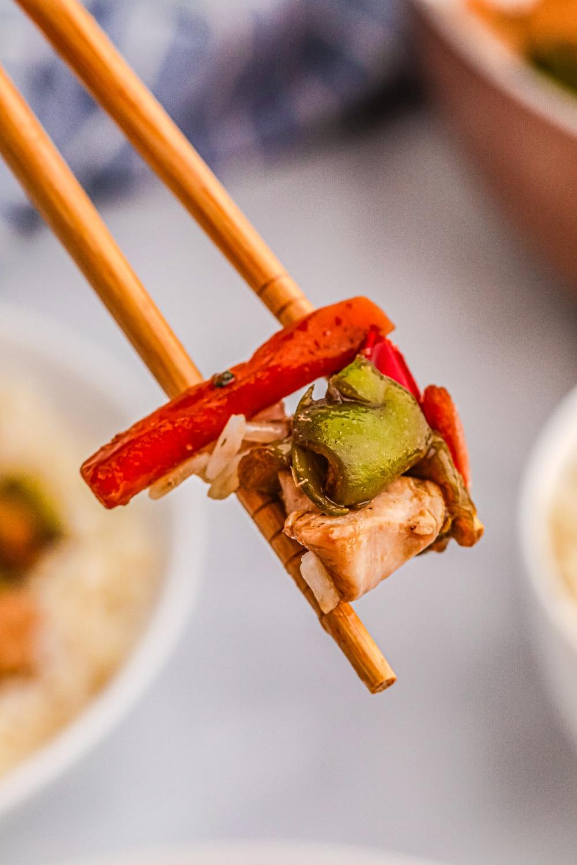 A single bite of stir-fry held by chopsticks.