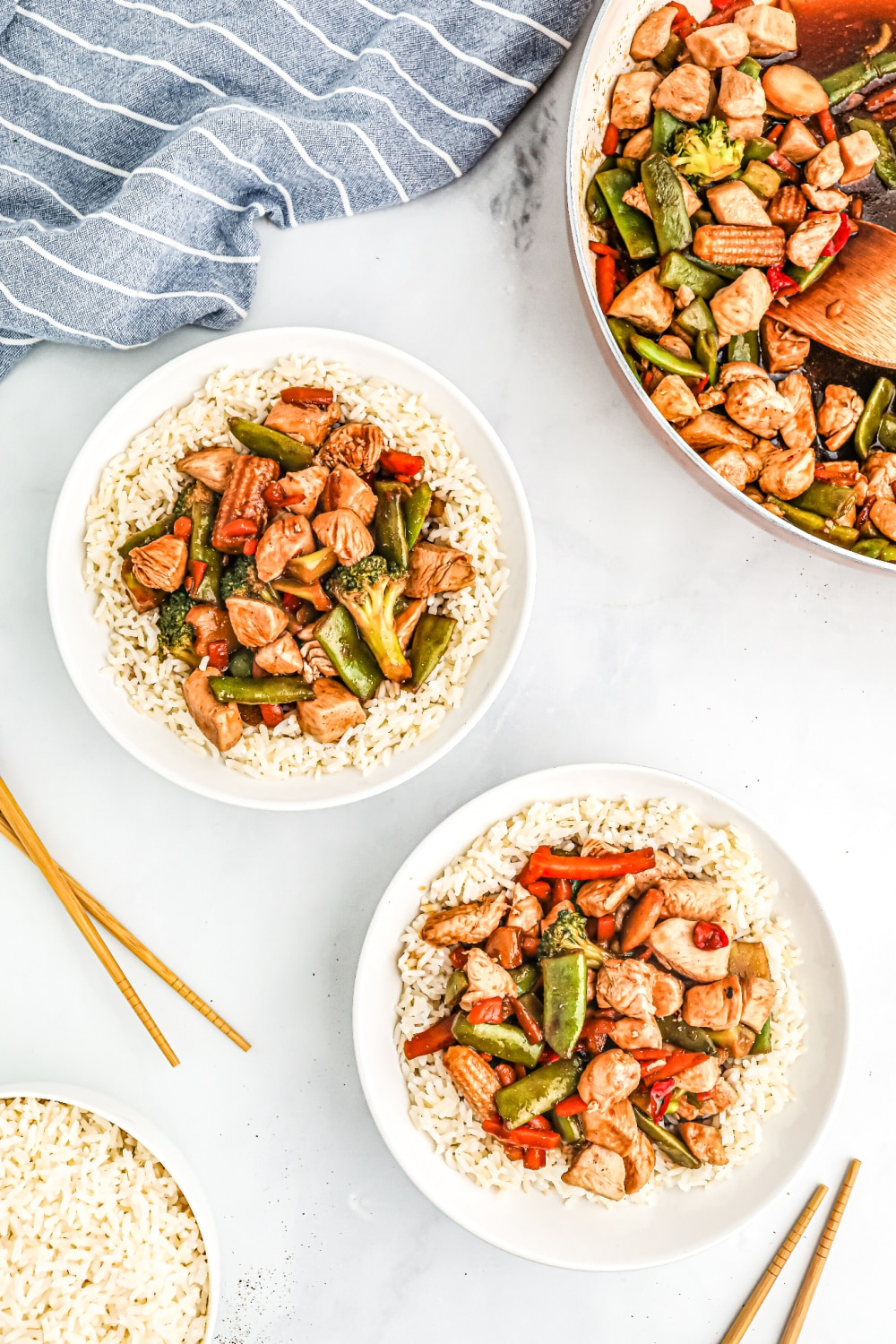 two white bowls of teriyaki chicken stir fry over rice next to a skillet of stir-fry.