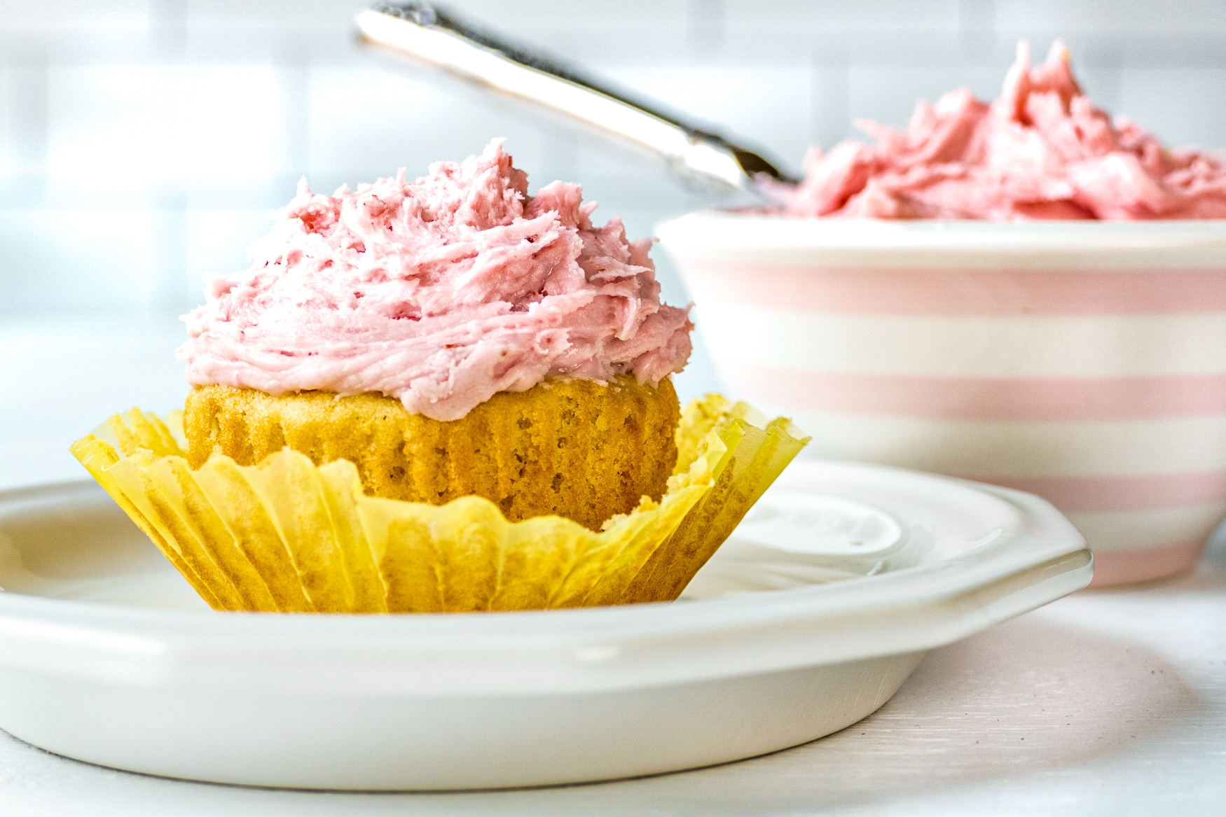 A frosted cupcake on a white plate sits in front of a bowl of raspberry buttercream.