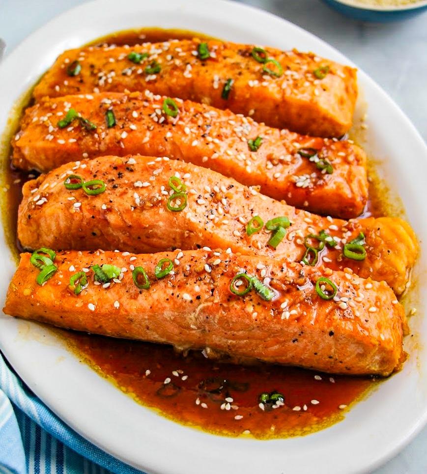 Four salmon fillets in honey garlic sauce on a white platter.