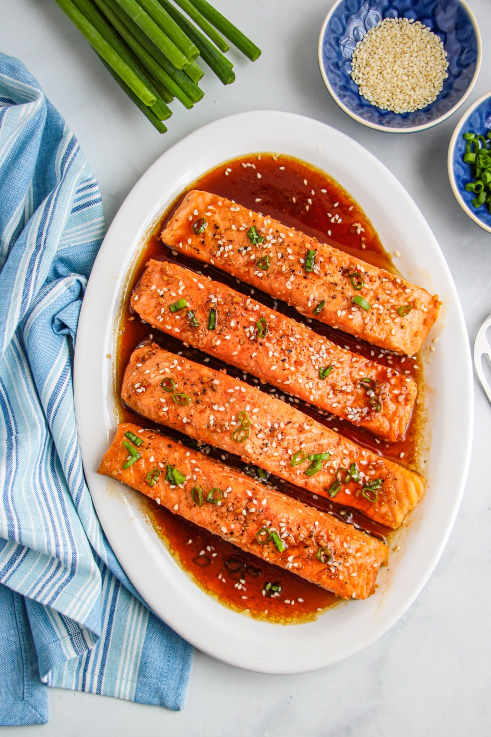 Honey Garlic Salmon fillets on a white platter with a blue dish towel on the left.