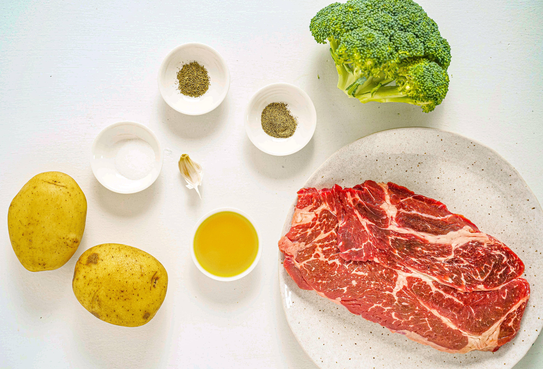 Raw ingredients: steak, hear of broccoli, potatoes and seasonings.