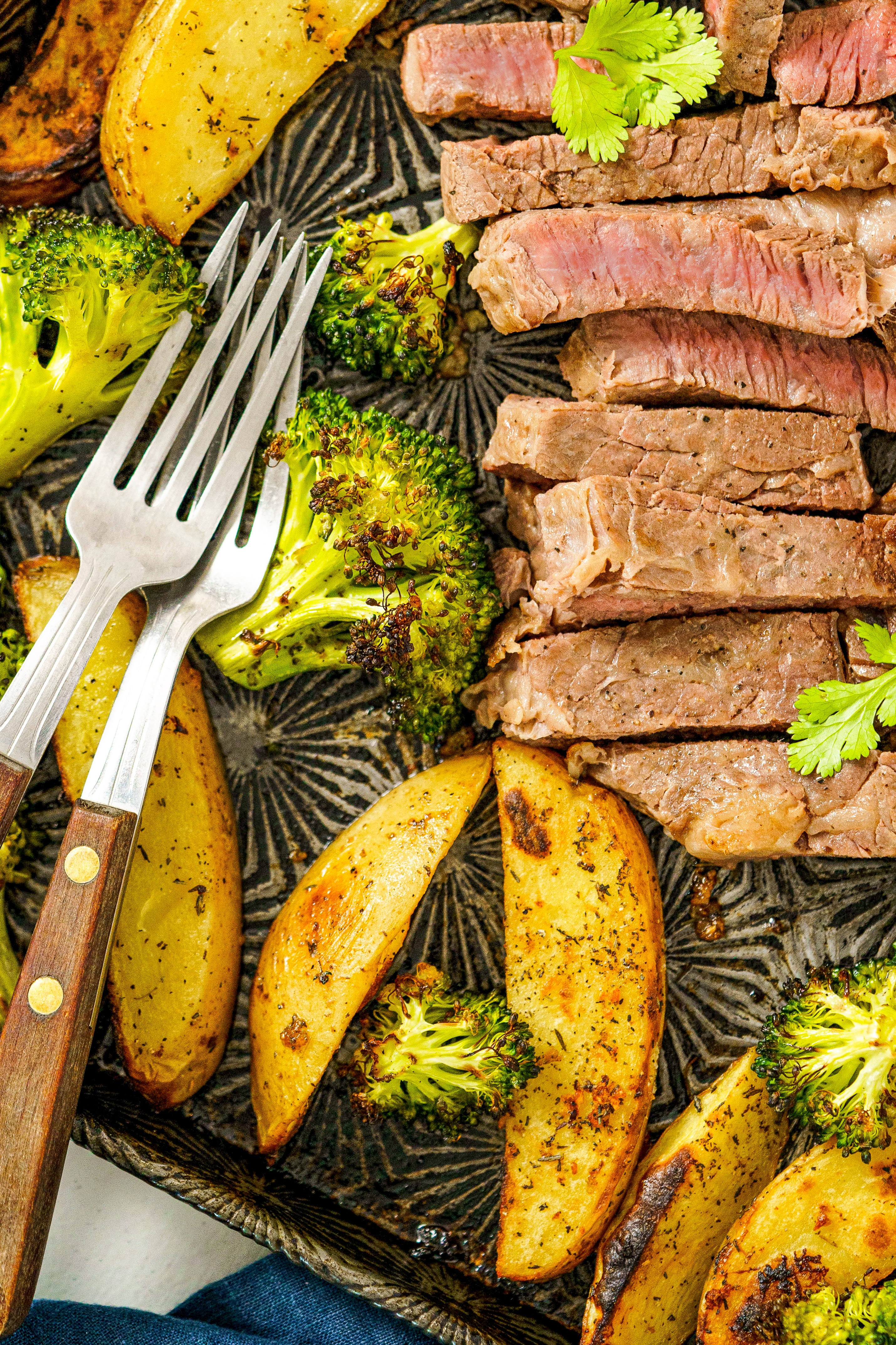 Steak, potato wedges and roasted broccoli on a sheet pan.