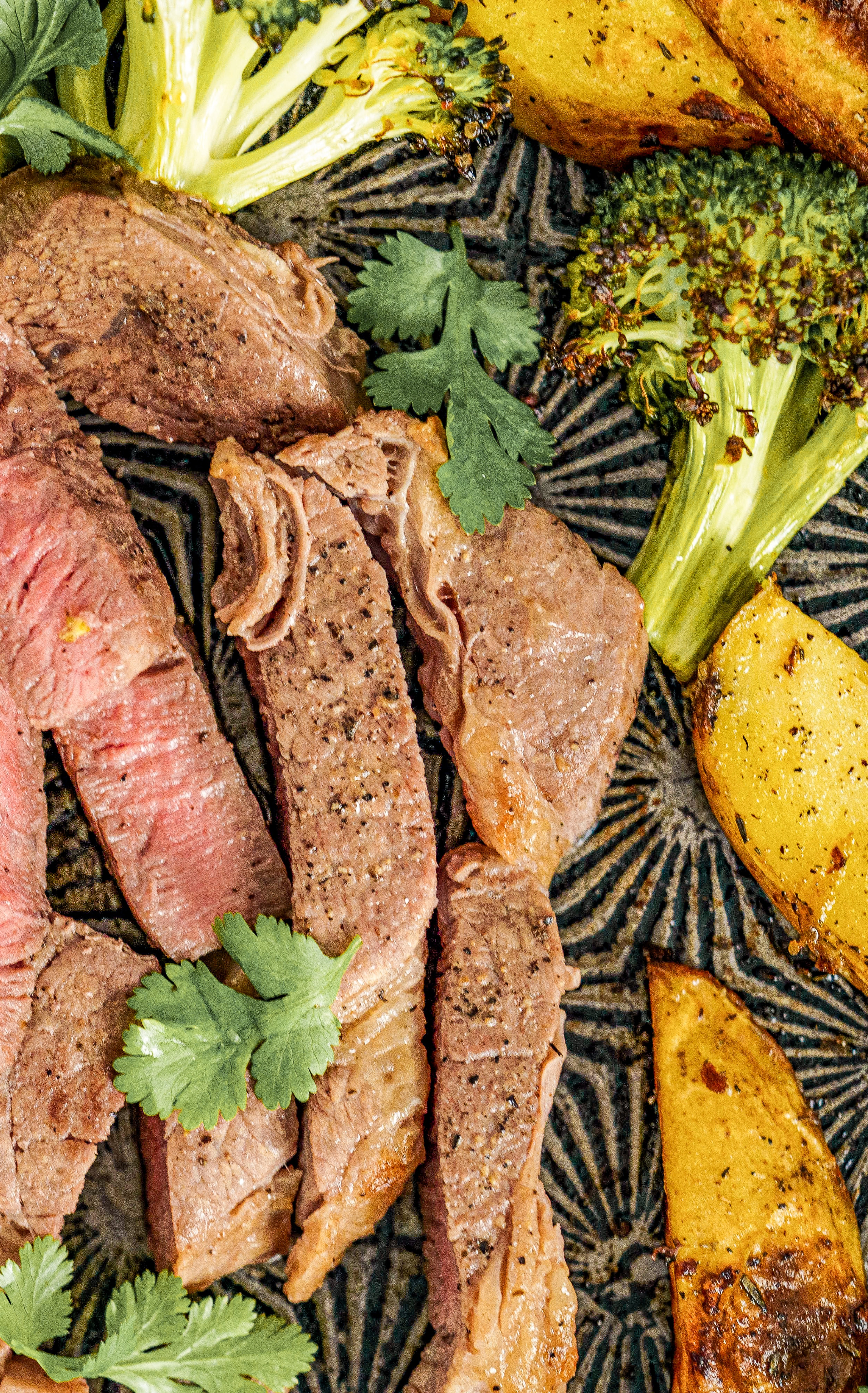 Sliced steak cooked medium garnished with parsley leaves.