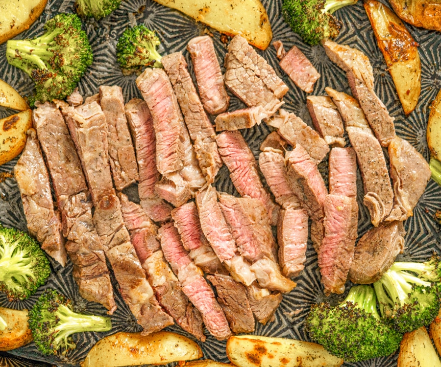Sliced steak surrounded by broccoli and potatoes on a sheet pan.