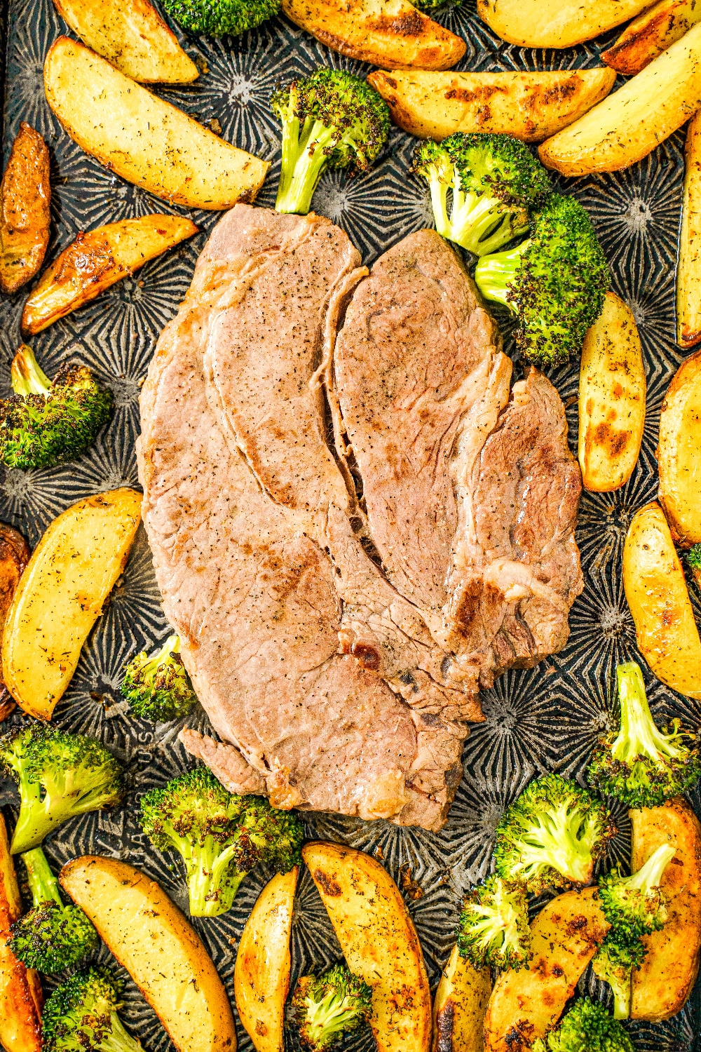 Prepared steak sounded by a bed of potatoes and broccoli on a sheet pan.
