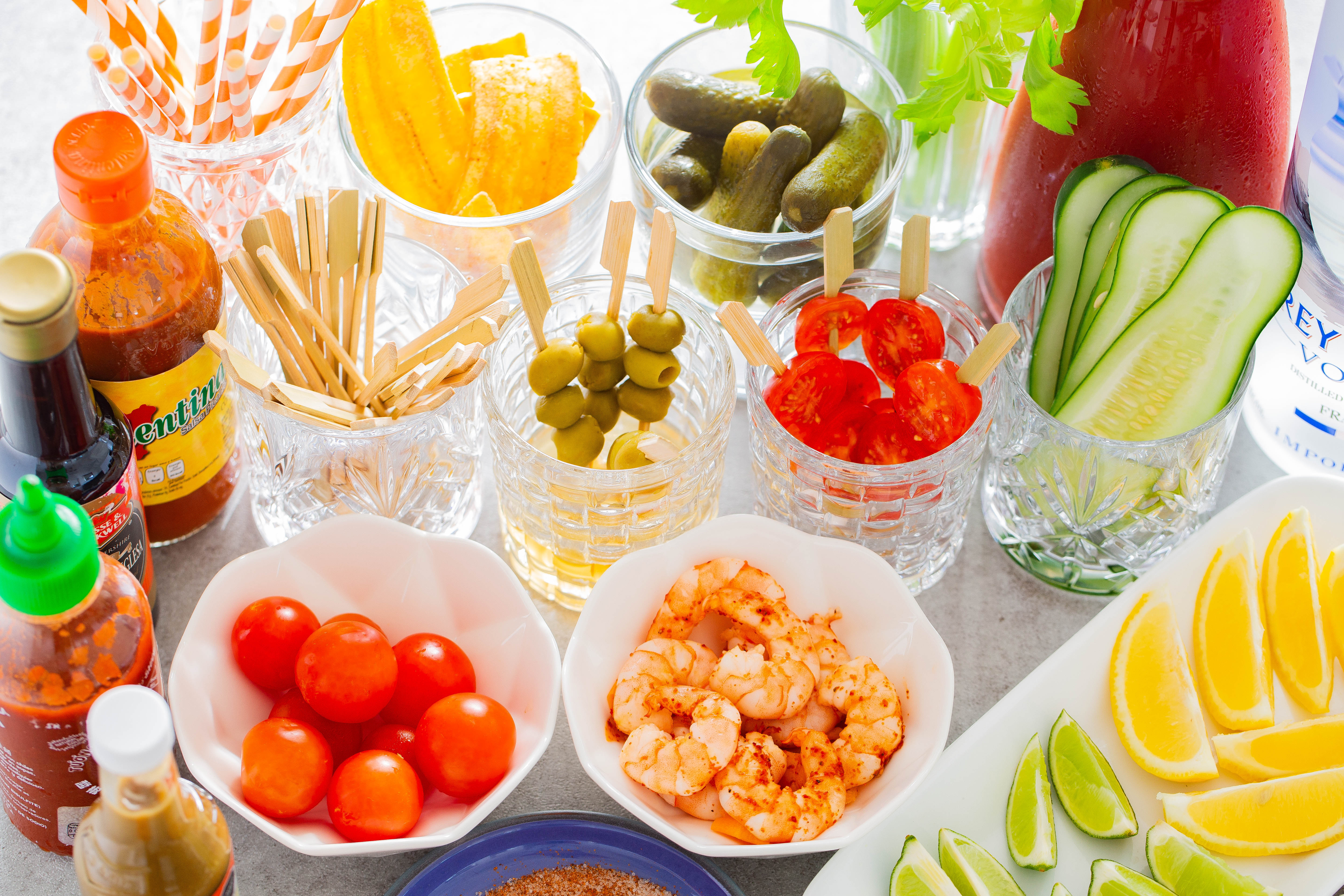 Straws, kosher pickles, celery, Bloody Mary mix, dill pickles, cherry tomatoes, olives and shrimp played out in clear bowls to create a Bloody Mary Bar.