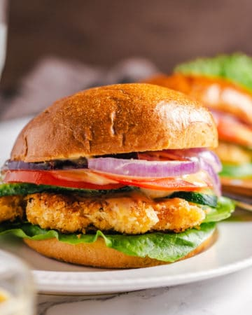 Crispy Chicken Sandwich garnished with red onion, tomatoes and lettuce on a white plate.