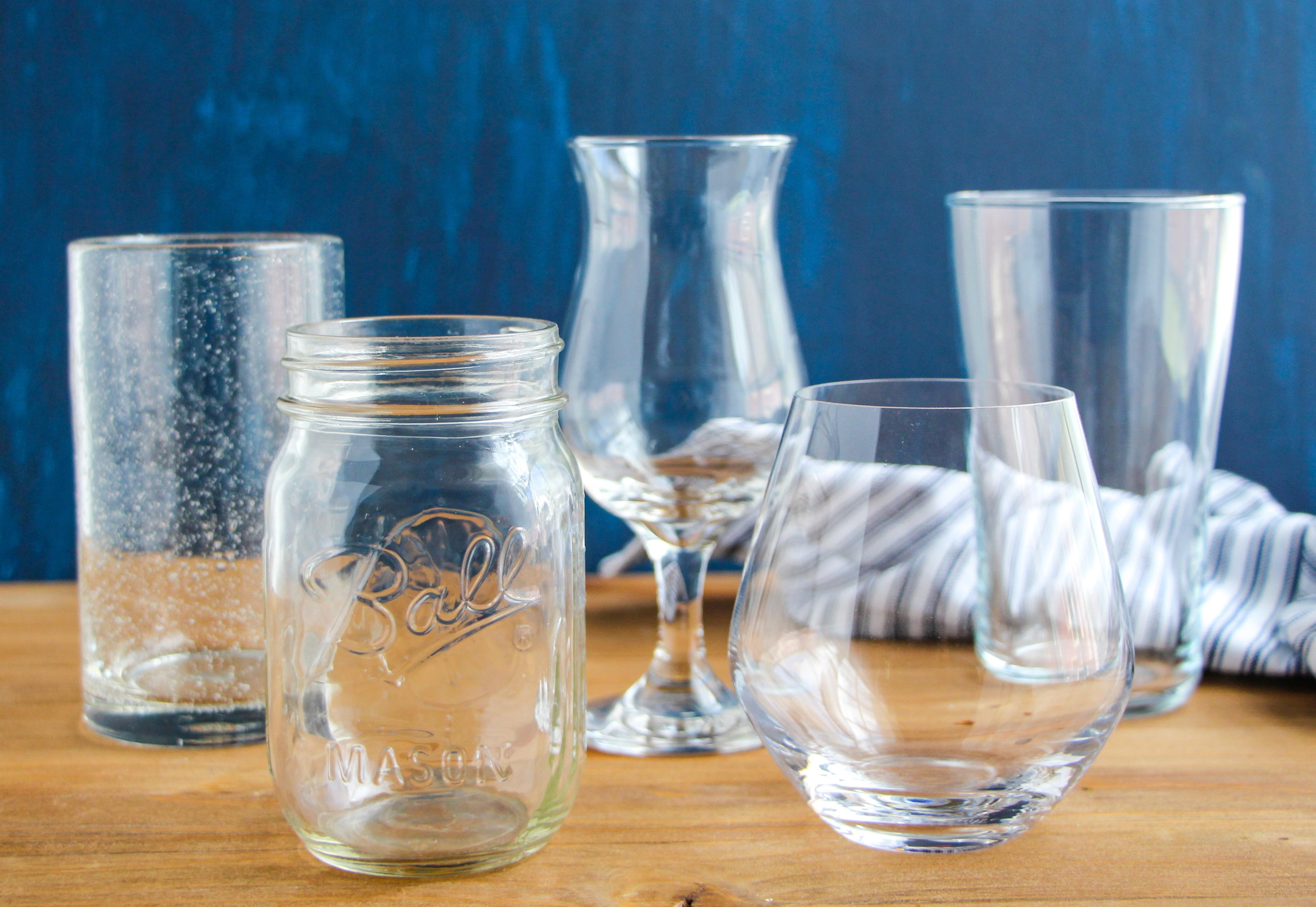 Empty drinking glass, mason jar, cocktail glass, stemless wine glass, rocks glass on a wooden tabletop.