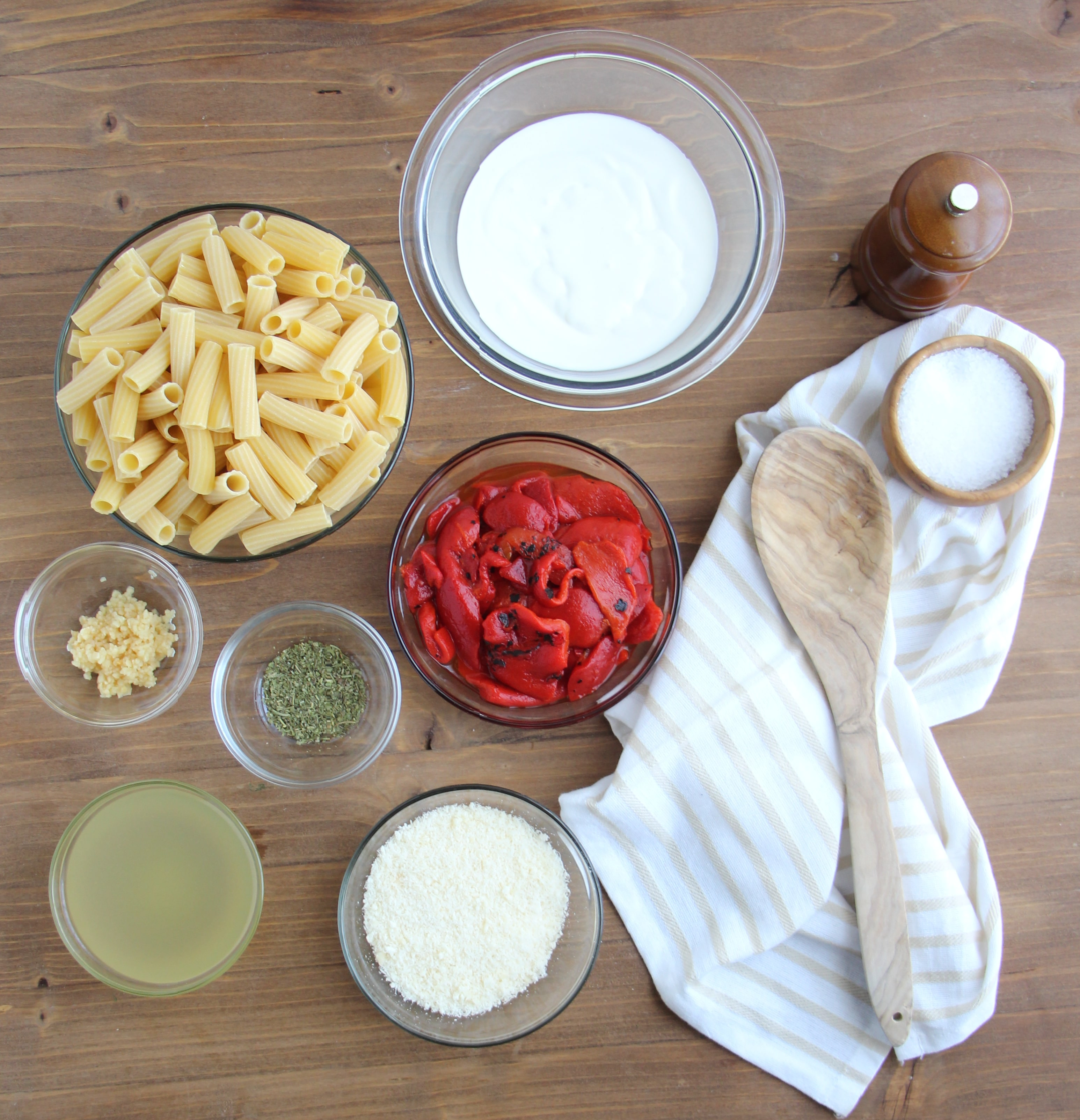 Ingredients needed to make Roasted Red Pepper Sauce measured into clear glass bowls on a wood background.