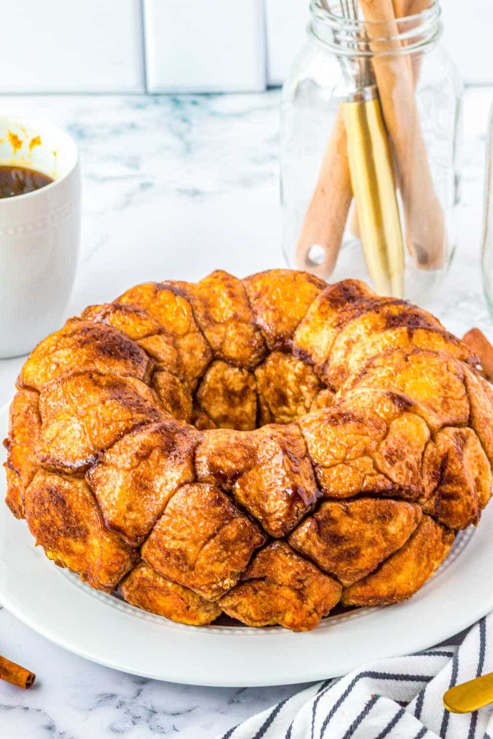 Fresh from the pan Monkey Bread on a white plate next to a blue and white striped towel.