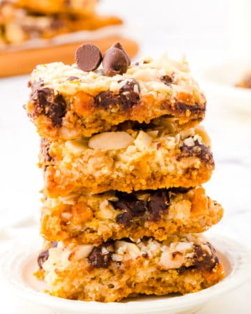 Three Hello Dolly Bars stacked on top of each other on a white saucer.